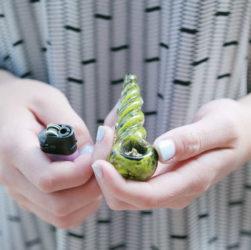 Fille qui tient un briquet et une pipe à cannabis